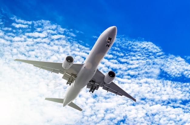 Белый большой пассажирский самолет в голубом небе.