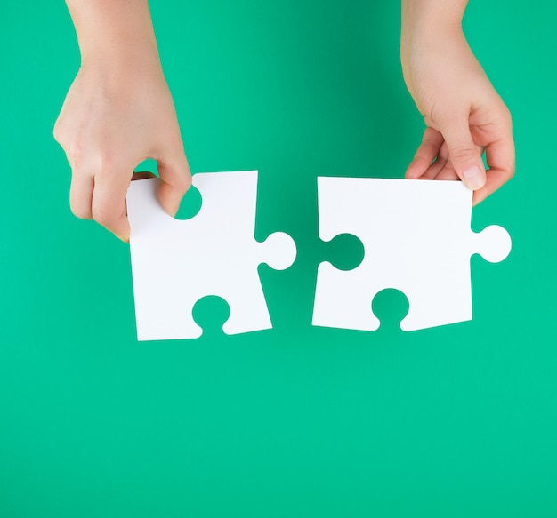 White big puzzles in female hand on green background