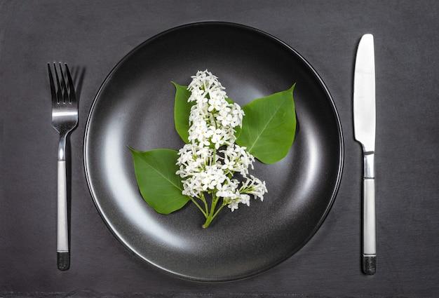 Белая черемуха цветущая ветвь на черной тарелке со столовыми приборами на фоне доски обслуживания черного сланца. вид сверху. минималистичная сезонная аллергия во время весеннего цветения.