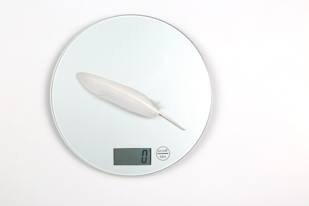 White bird feather is weighed on a digital scale