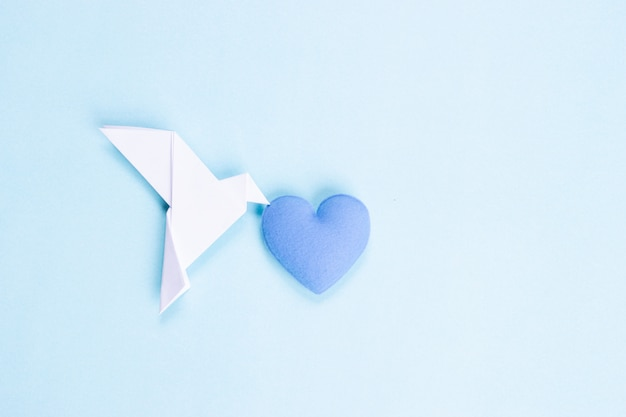 White bird made from paper carrying blue heart. international day of peace.