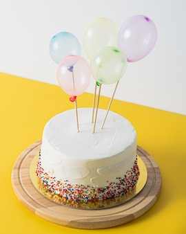 White birthday cake and colorful balloons