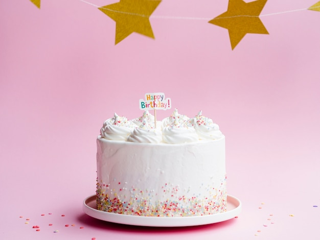 White birthday cake and golden stars