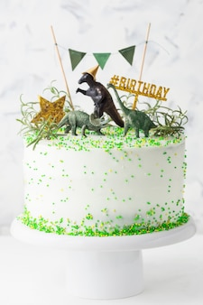 White birthday cake with green decorations, gold star and dinosaurs on a cake stand