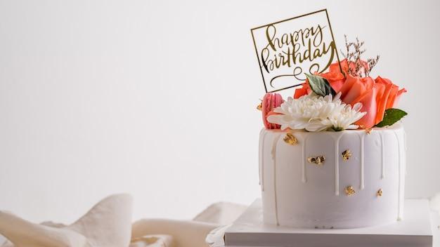 핑크 장미 꽃과 흰색 생일 케이크입니다.