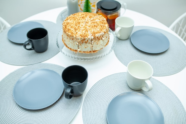 White biscuit cake cut on a stand on a serving table. around the cake lay out plates with cups and tea