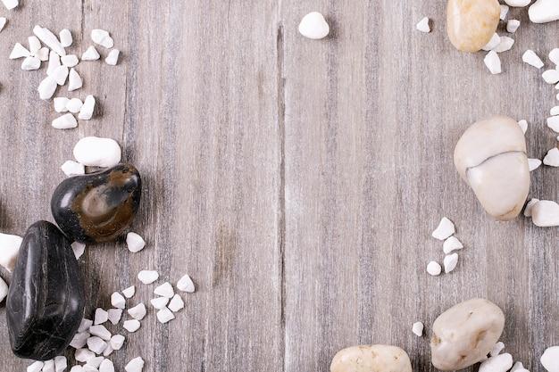 Белые, черные декоративные камни и галька на сером деревянном фоне. вид сверху, плоская планировка. копировать пространство