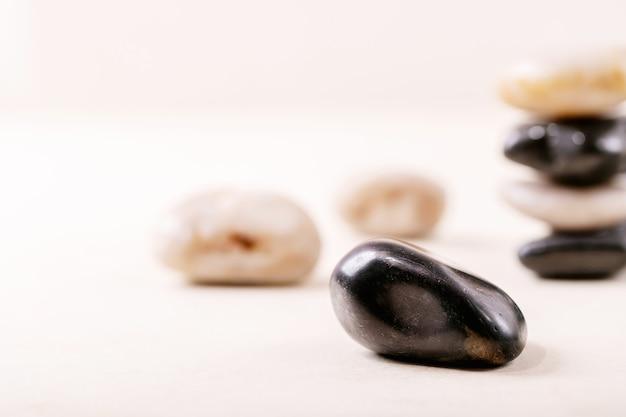 Белые, черные декоративные камни и галька на сером деревянном фоне