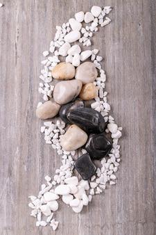 Белые, черные декоративные камни и галька на серой деревянной поверхности. вид сверху, плоская планировка. копировать пространство