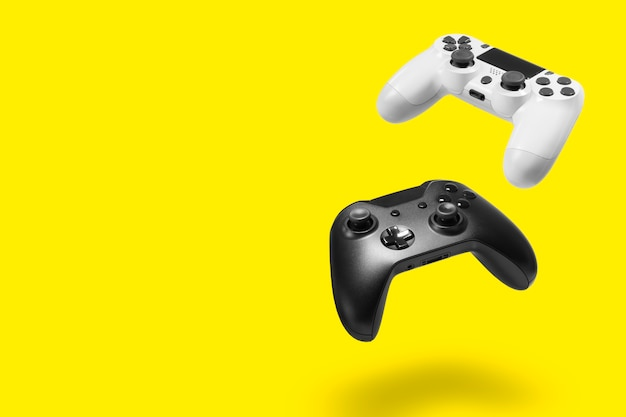 White and black game controllers on yellow wall