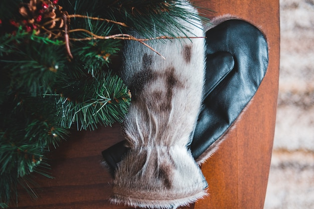White-and-black gloves near christmas tree with brown pinecone