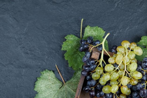 Uva bianca e nera con foglie su sfondo scuro. foto di alta qualità