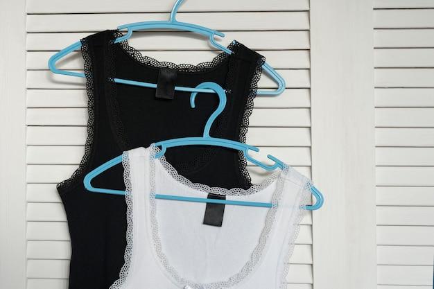 White and black jerseys on the hanger. white shutters