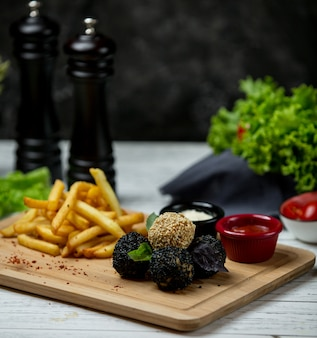 White and black sesame balls with french fries on wooden board