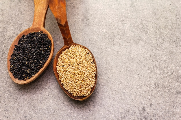 White and black sesame seeds in wooden spoons