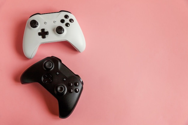 White and black two joystick gamepad, game console on pastel pink colourful trendy pin-up .