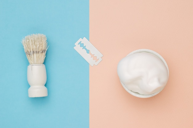 White blade, foam and shaving brush on beige and blue background.