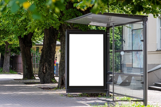 White blank advertising banner at a public transport stop of a trolley bus in the city near the park