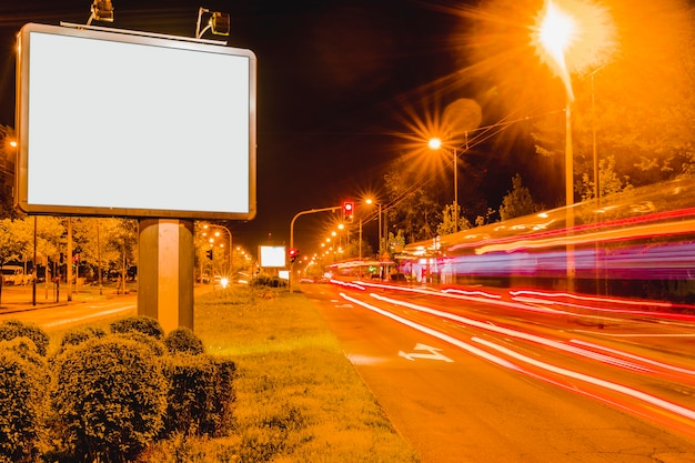 White blank billboard near the roadside with rush hour traffic light trails