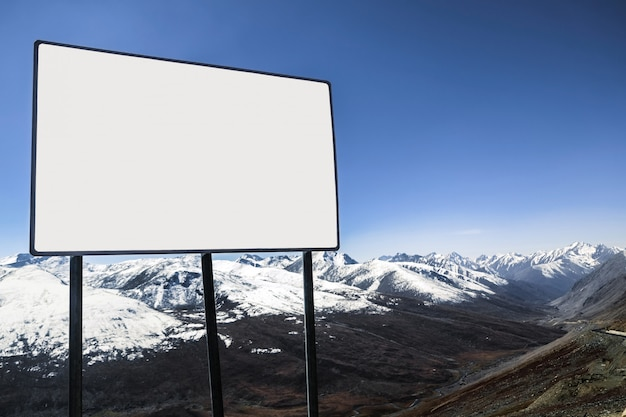 White blank billboard with a view of clear blue sky and snow capped mountain range.