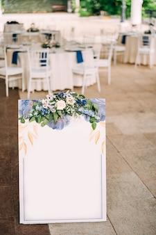 장신구와 꽃으로 장식 된 흰색 빈 보드는 입구에 서 있습니다.