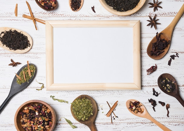 White blank board surrounded with herbs on white textured backdrop