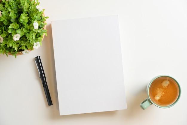ペン、コーヒーカップ、白い背景の上の植物と白い空白の本の表紙のモックアップ。上面図