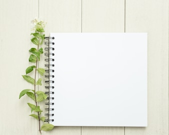White blank book with a green leaf.White wooden table,