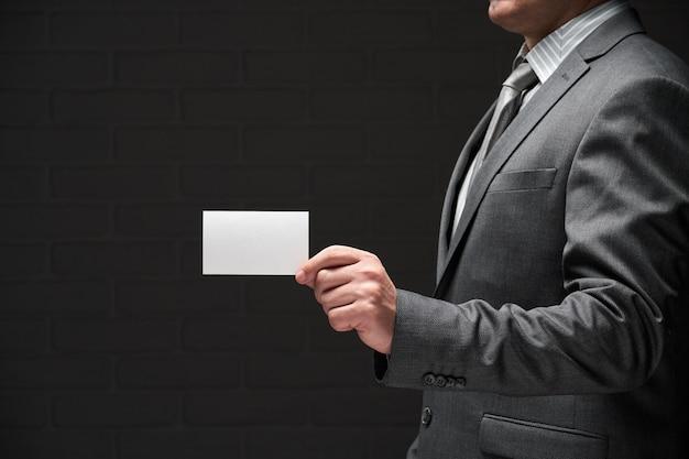 ビジネスマンの手、灰色のスーツ、暗い壁の背景に白い空白の名刺のクローズアップ