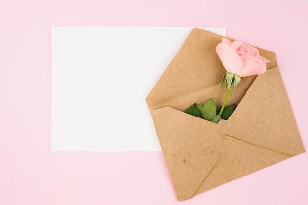 Белая пустая карточка и коричневый конверт с розой на розовом фоне