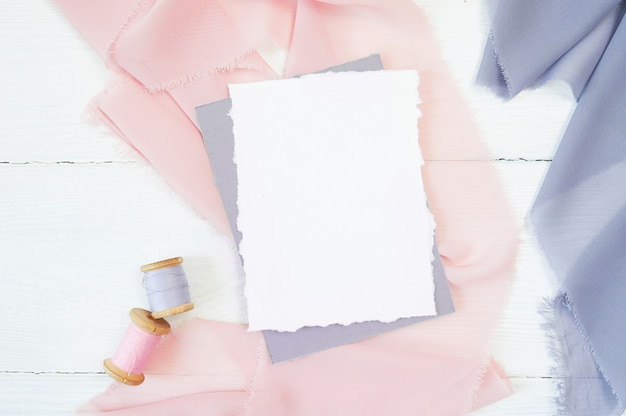 White blank card on a background of pink and blue fabric on white