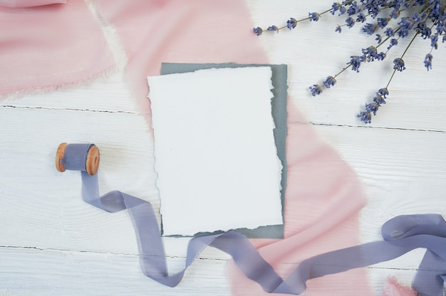 White blank card on a background of pink and blue fabric with lavender flowers