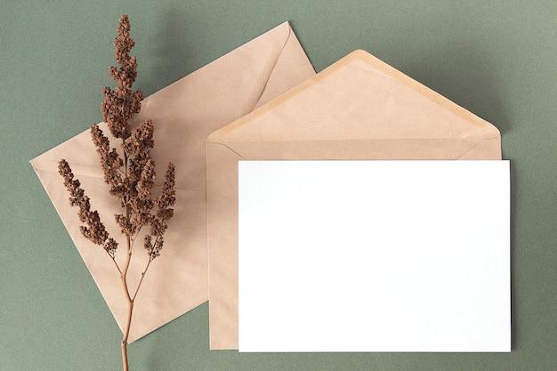 白い空白のカード、クラフト封筒、ドライフラワーは緑の背景に植えます。上面図フラットレイモックアップコピースペース。