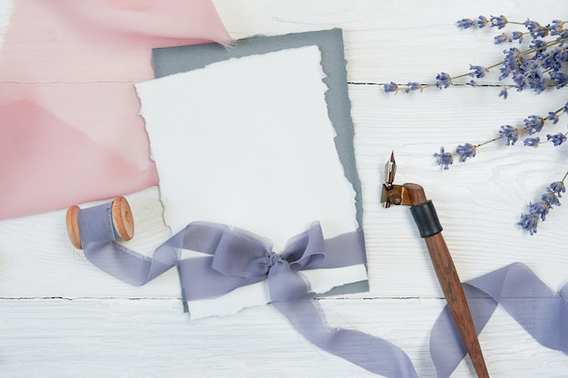 White blank card ribbon bow on a background of pink and blue fabric with lavender flowers and calligraphic pen