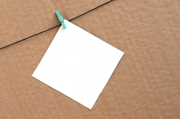 White blank card on rope on a brown cardboard background