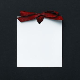 暗い背景に赤いリボンと白い空白のカード。テキスト用の空の場所