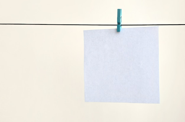 White blank cards on rope, light wall background