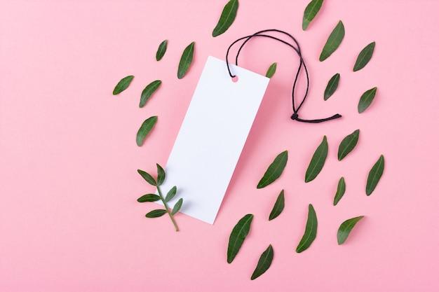 Белая пустая бирка одежды с черной веревкой на розовом фоне. маленькая зеленая ветка с листьями