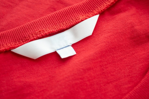 White blank clothing tag label on new red cotton shirt fabric texture background