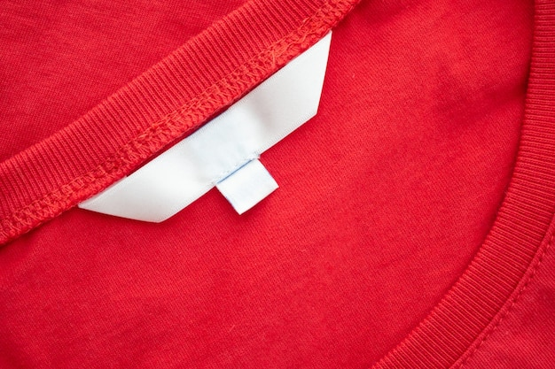 새 빨간면 셔츠 패브릭 질감 배경에 흰색 빈 의류 태그 레이블