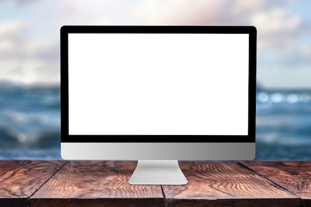 Белый пустой дисплей компьютера на деревянном столе против запачканного морского пейзажа естественного с боке, космосом экземпляра. концепция удаленной работы.