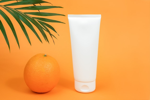 White blank cosmetic bottle, tube of cream, lotion for body, face or hand, orange fruit and branch of palm.