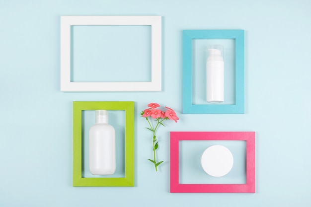White blank cosmetic bottle, tube, jar, one flower and bright frames on blue
