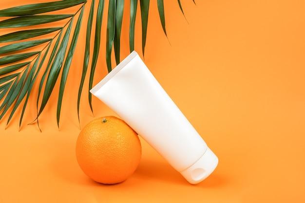 Белая пустая косметическая бутылка, тюбик крема, лосьон для тела, лица или рук, апельсиновый фрукт и ветвь пальмы. концептуальная косметика с витамином с, антиоксидантами или антицеллюлитом. мокап вид спереди.
