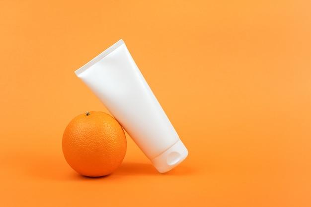 白い空白の化粧品ボトル、クリームのチューブ、体、顔、または手のためのローション、オレンジ色の果物。ビタミンc、抗酸化物質を含む化粧品のコンセプト