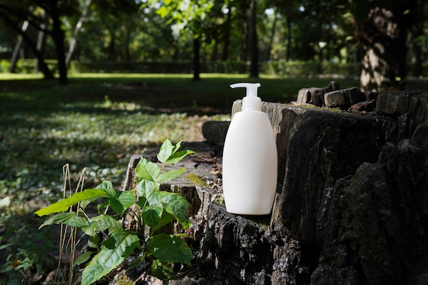 녹색 잎이 있는 나무 배경에 크림, 보습 로션 또는 샴푸가 있는 흰색 빈 화장품 병. 천연 유기농 스파 화장품 뷰티 개념입니다. 모형