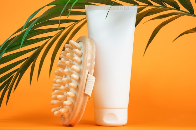 White blank cosmetic tube of cream or body lotion, orange fruit, wooden anticellulite massager and green branch palm.