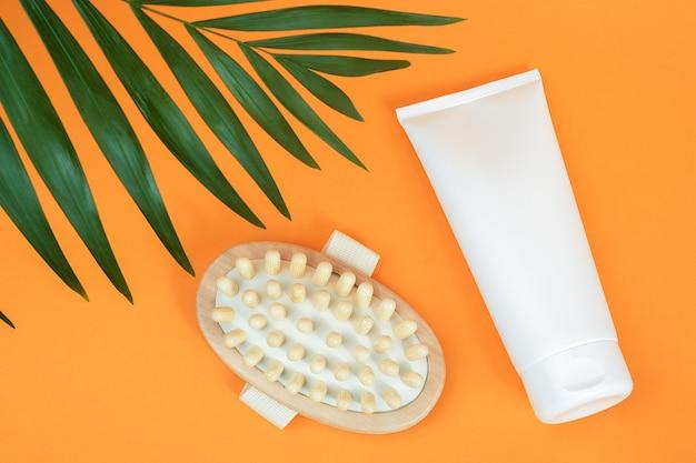 クリームやボディローションと木製のアンチセルライトマッサージャー、オレンジ色の背景にヤシの葉の白い空白の化粧品のチューブ。