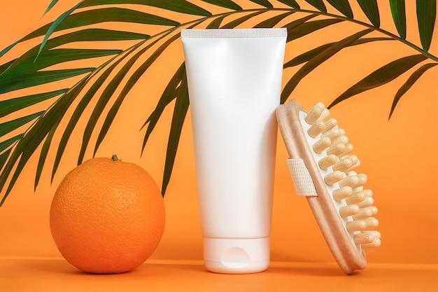 Белый пустой косметический тюбик крема или лосьона для тела, апельсиновый фрукт, деревянный антицеллюлитный массажер и зеленая ветвь пальмы. концепция борьбы с целлюлитом. мокап вид спереди.