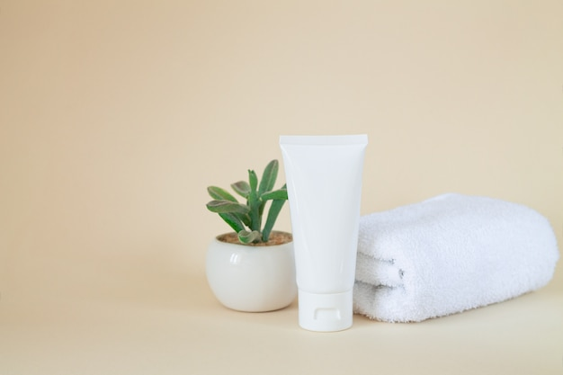 White blank cosmetic tube standing next to plant and towel